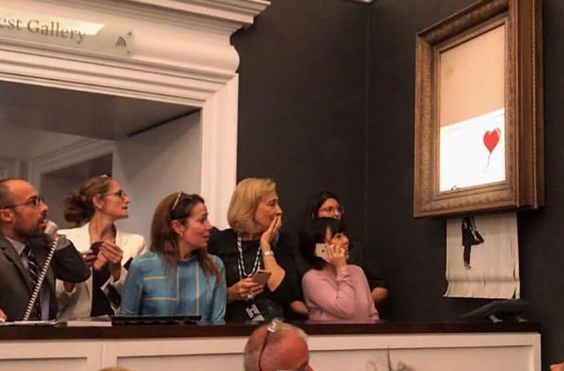 Banksy's Girl With Ballon shreds itself after being bought at a Sotheby's auction